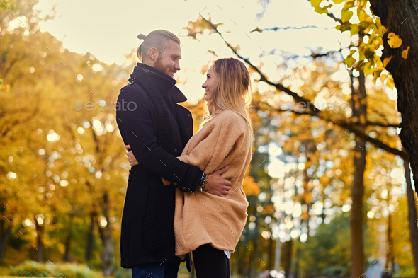 Redhead male hugs cute blonde female in autumn wild nature backg - Stock Photo - Images