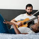 Man Playing Guitar And Woman Singing Song In Bedroom - PhotoDune Item for Sale