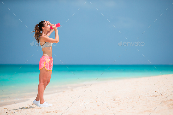 Fit young woman doing exercises on tropical white beach in her sportswear - Stock Photo - Images