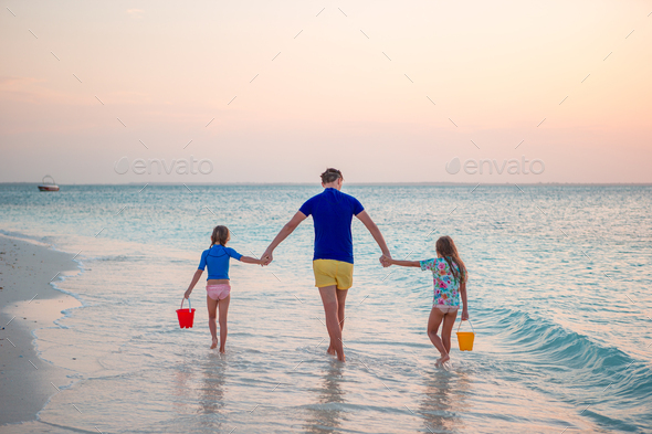 Happy father and his adorable little daughters at tropical beach having fun - Stock Photo - Images