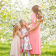 Adorable little girls with young mother in blooming cherry garden on beautiful spring day - PhotoDune Item for Sale