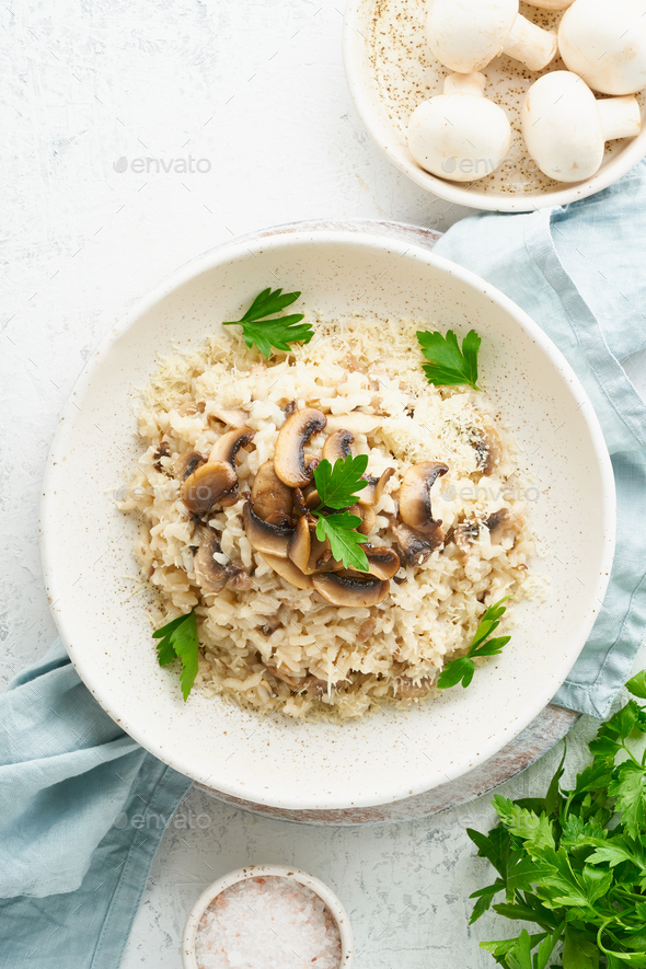 Risotto with mushrooms in plate. Rice porridge with mushrooms and parsley - Stock Photo - Images