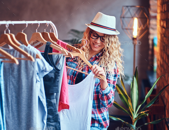 A woman chooses fashionable clothes on the coat rack. - Stock Photo - Images