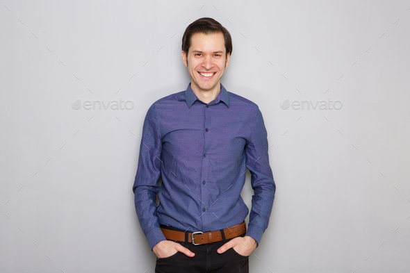 handsome young businessman standing by gray wall smiling - Stock Photo - Images