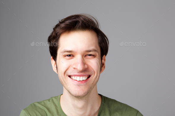 Close up happy young man standing by gray wall - Stock Photo - Images