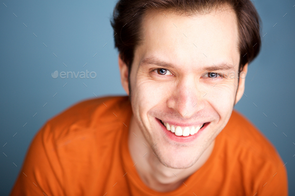Close up fashionable man smiling on blue background - Stock Photo - Images