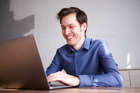 Close up smiling business man working from home on laptop - Stock Photo - Images