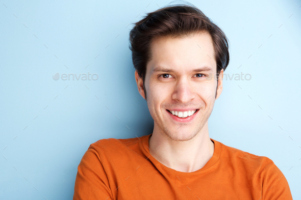 Close up happy man in orange shirt on blue background - Stock Photo - Images