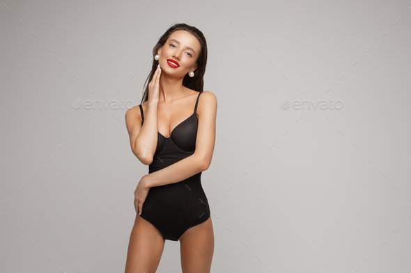 Healthy young woman in swimsuit poses for the camera, picture isolated on white background - Stock Photo - Images