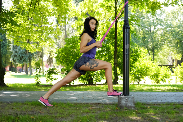 Female doing exercising with fitness trx straps in a summer park - Stock Photo - Images