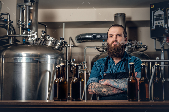 A man manufacturer presenting beer in the microbrewery. - Stock Photo - Images
