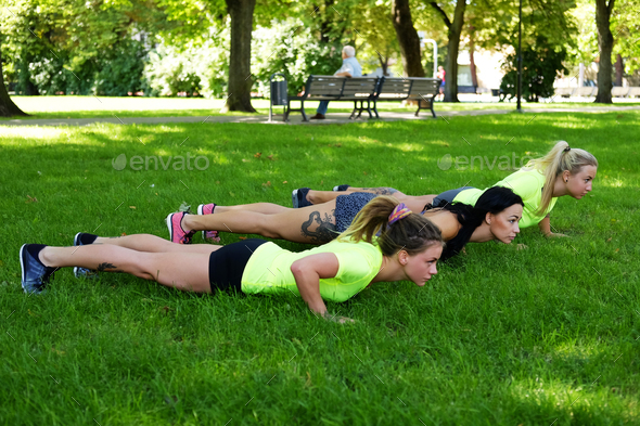 Females warming up on a lawn in summer park. - Stock Photo - Images