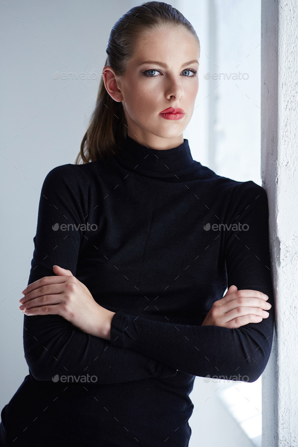 Portrait of brunette woman with crossed arms. - Stock Photo - Images