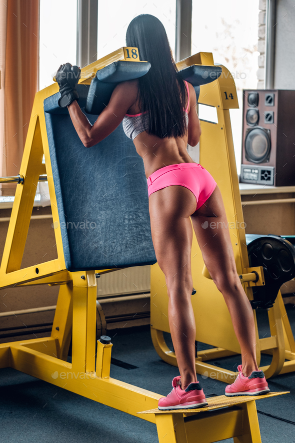 Female doing workouts on legs exercising machine. - Stock Photo - Images