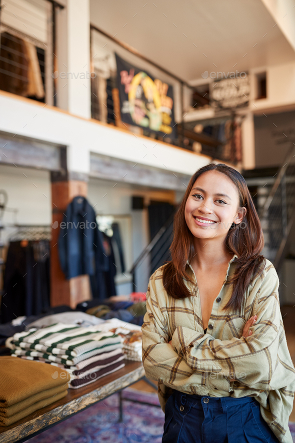 Portrait Of Smiling Female Owner Of Fashion Store Standing In Front Of Clothing Display - Stock Photo - Images