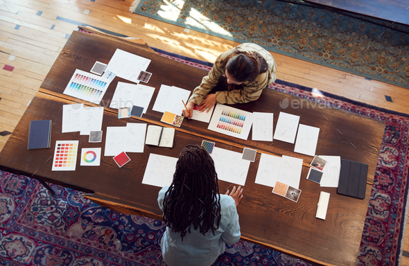Overhead View Of Two Women Having Creative Design Meeting Around Wooden Table In Office - Stock Photo - Images