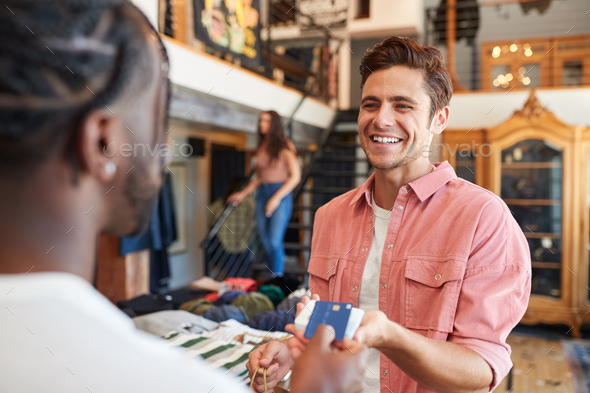 Man In Clothing Store Making Contactless Payment At Sales Desk Holding Credit Card To Reader - Stock Photo - Images