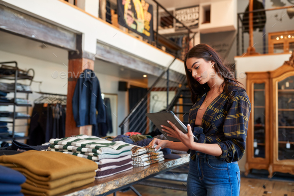 Female Owner Of Fashion Store Using Digital Tablet To Check Stock In Clothing Store - Stock Photo - Images