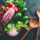 Various fresh colorful vegetables in a plate on a table with wooden kitchen utensils. Top view. - PhotoDune Item for Sale