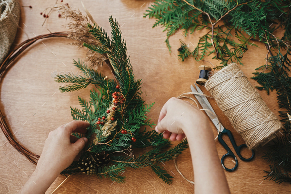Hands holding fir branches and pine cones, berries, thread, scissors on wooden table - Stock Photo - Images