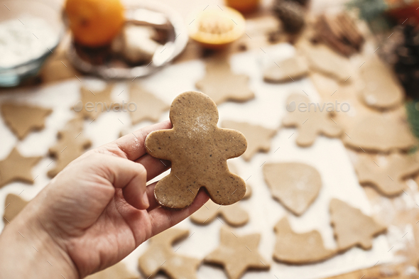Hand holding raw gingerbread man cookie on background of dough - Stock Photo - Images