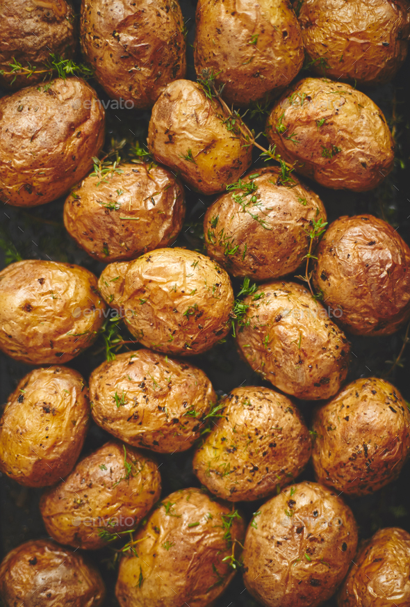 Oven baked whole potatoes with seasoning and herbs in metalic tray. Roasted potatoes in jackets - Stock Photo - Images