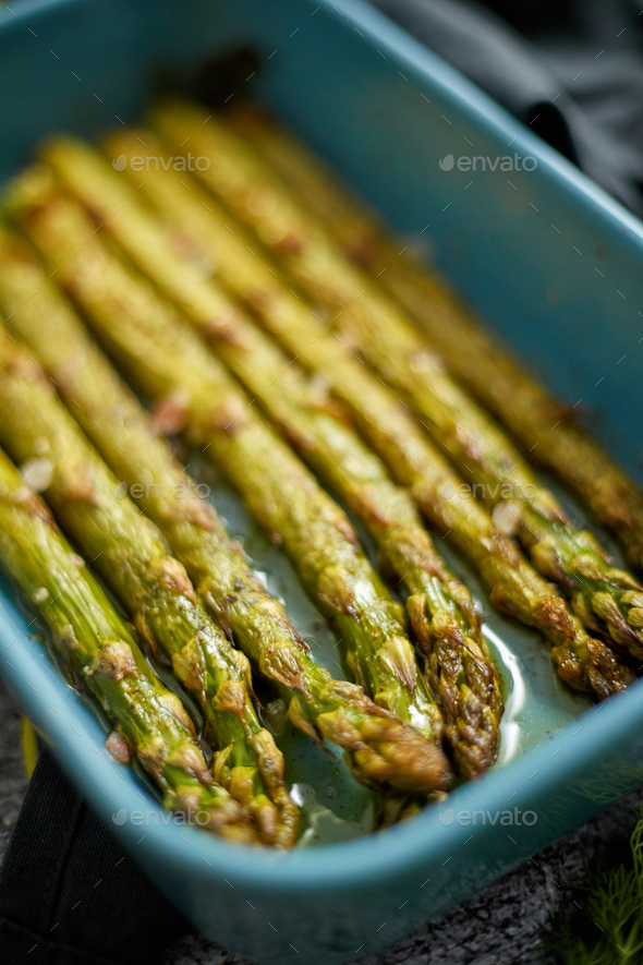 Close up with selective focus on roasted asparagus seasoned with salt, pepper, garlic - Stock Photo - Images