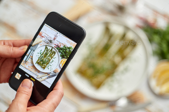 Woman taking picture of fresh prepared food with smartphone for social media. Roasted aparagus - Stock Photo - Images