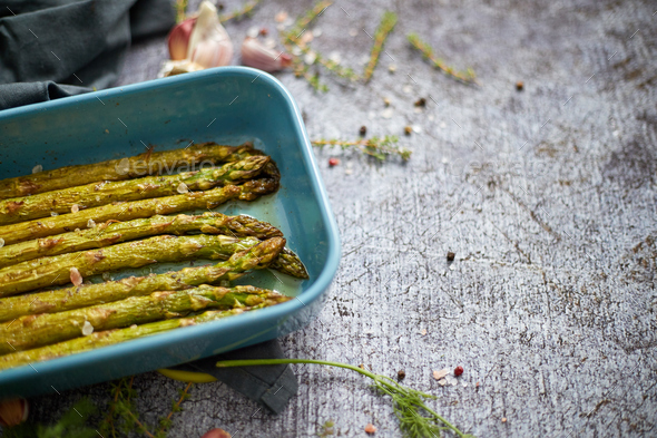 Roasted asparagus seasoned with salt, pepper, garlic and decorated with fresh herbs - Stock Photo - Images
