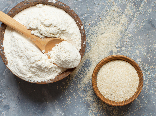 Raw fonio flour and seeds with a spoon on grey background - Stock Photo - Images
