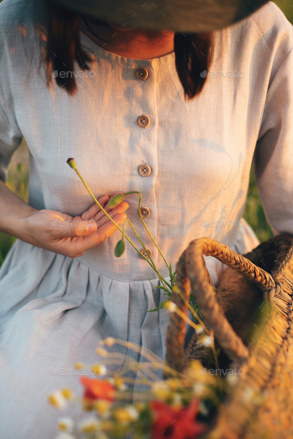 Stylish girl in linen dress gathering flowers in rustic straw basket - Stock Photo - Images