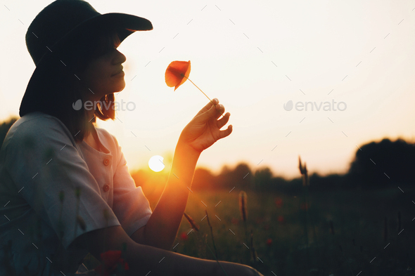 Silhouette of stylish girl in linen dress holding poppy flower in meadow in sun light - Stock Photo - Images