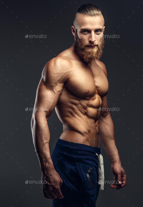 Shirtless bodybuilder with beard posing. - Stock Photo - Images