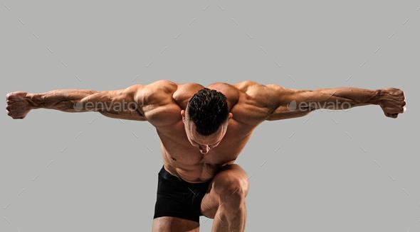 Bodybuilder on grey background - Stock Photo - Images