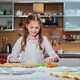 Cheerful little girl cooking dough at the kitchen. - PhotoDune Item for Sale