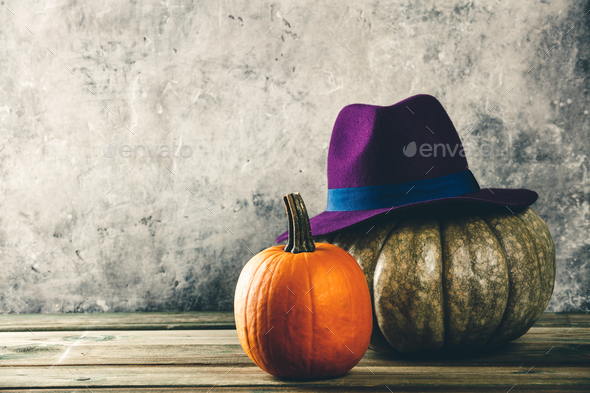 Autumn background with pumpkins and purple felt hat - Stock Photo - Images