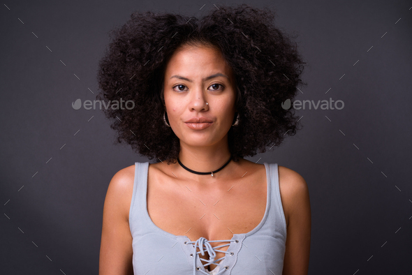 Young beautiful multi-ethnic African American woman against gray background - Stock Photo - Images