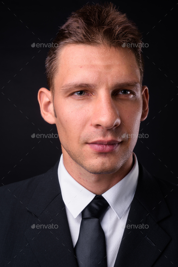 Studio shot of businessman against black background - Stock Photo - Images