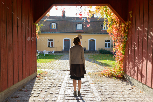 Back view of young woman standing in wooden entrance of elegant suburban house - Stock Photo - Images