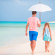 Young father and his little daughter walking under umbrella on white sand beach - PhotoDune Item for Sale