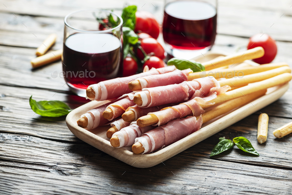 Italian antipasto with brad sticks and pork ham - Stock Photo - Images