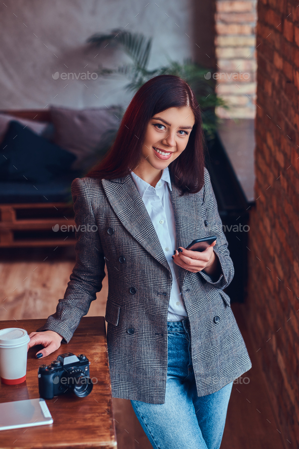 Portrait of a young female photographer works with a phone leani - Stock Photo - Images