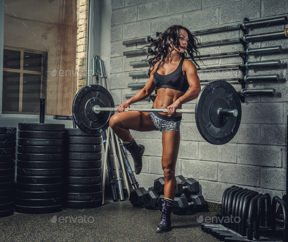 Female with barbell in a gym club. - Stock Photo - Images