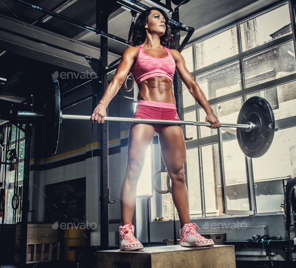 Sexy sporty female in pink sportswear holding barbell. - Stock Photo - Images