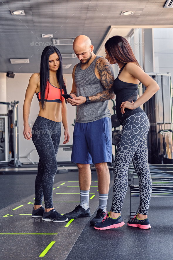 Two women and a man using a smart phone in a gym club. - Stock Photo - Images
