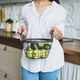 Young woman in white shirt hold basket with green fruits and vegetables in hands on kitchen - PhotoDune Item for Sale