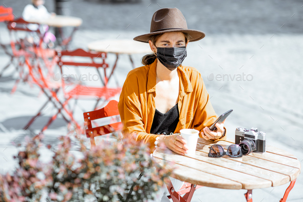 Woman in facial protective mask at the cafe outdoors - Stock Photo - Images