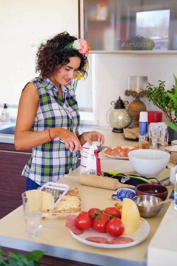 Positive brunette female makes dough in a kitchen. - Stock Photo - Images