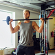 Sporty male in sportswear holds barbell over TRX stand background in a gym club. - PhotoDune Item for Sale