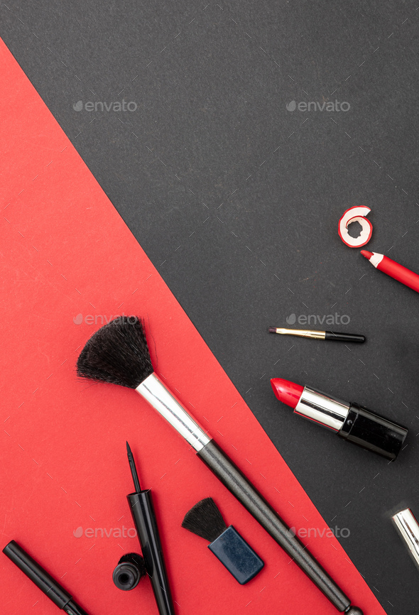 Make-up cosmetics accessories against red and black background - Stock Photo - Images